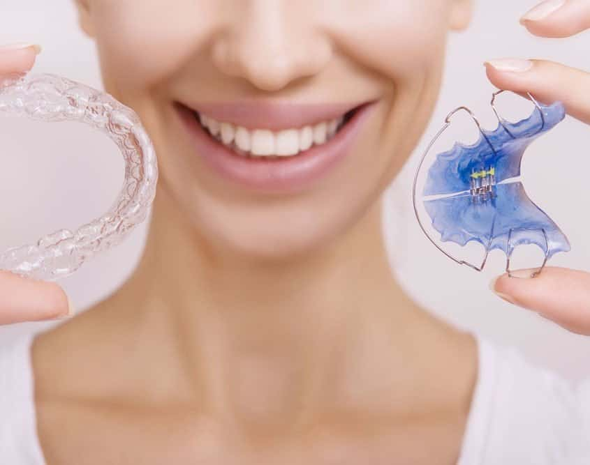 adult-holding-invisalign-braces-and-retainer
