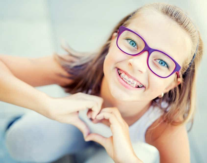 kid-with-braces-making-a-heart